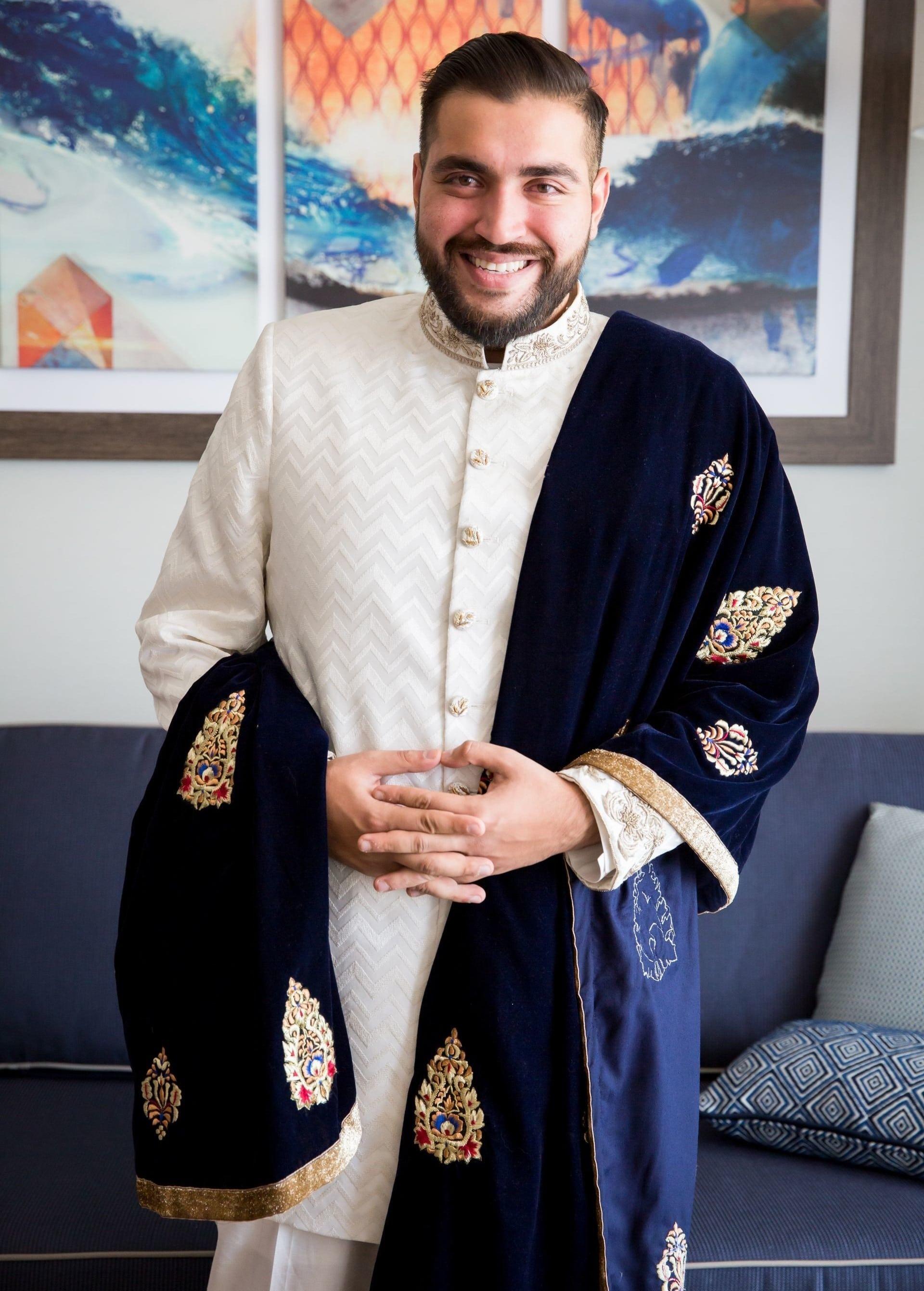 Indian groom wearing sherwani with black stole